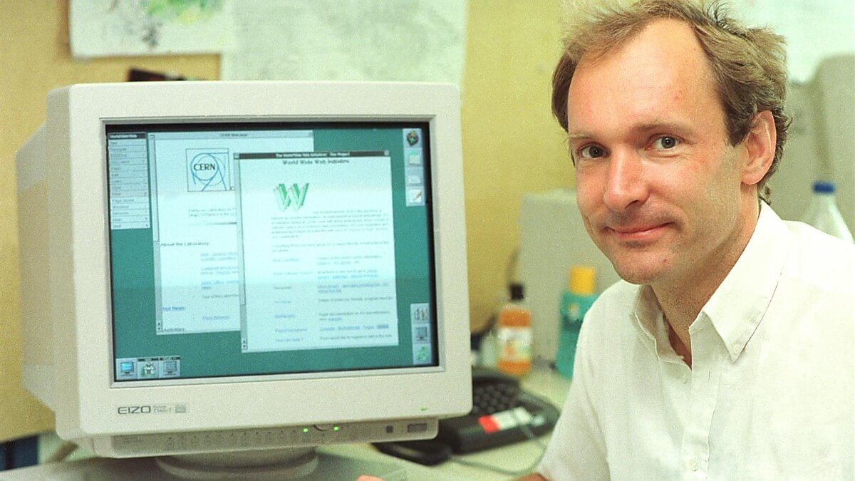 Tim Berners-Lee sitting in front of a computer showing the first website