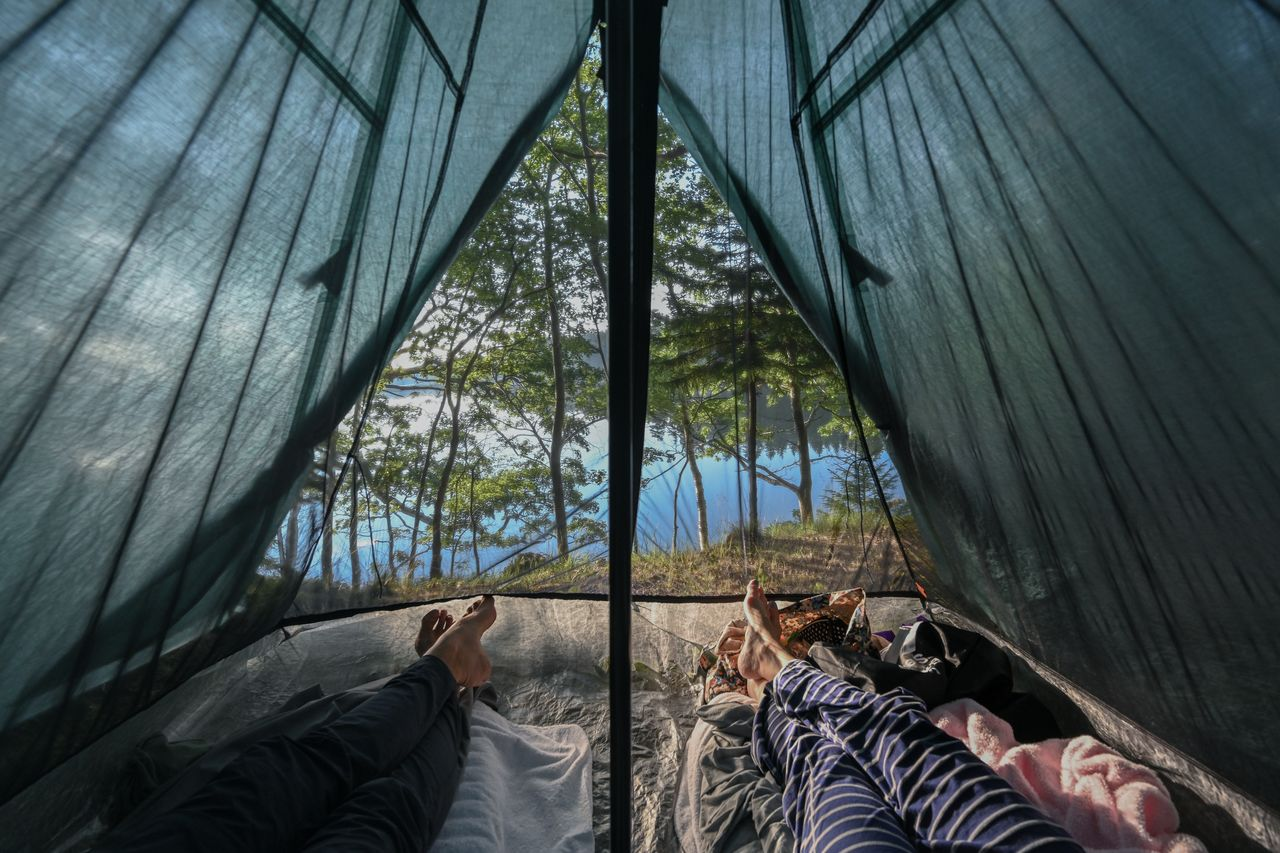 View from inside our tent: our legs are shown in the foreground and the ocean in the background.