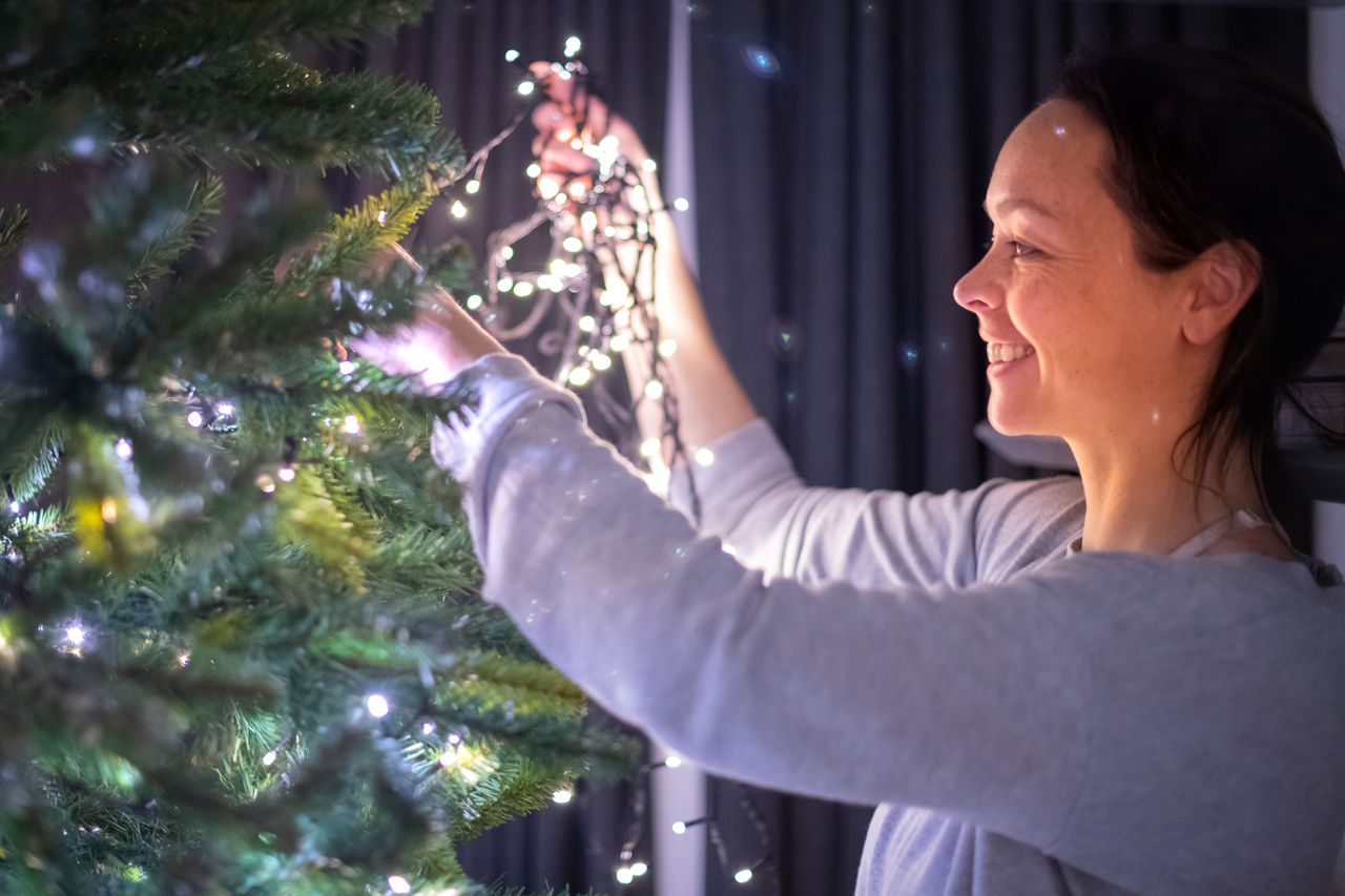 Vanessa hanging the lights in the Christmas tree