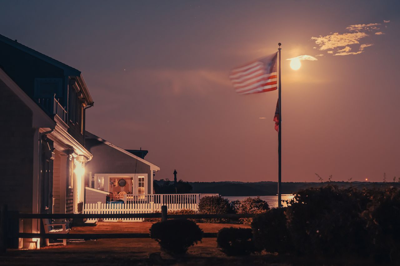An American flag waving in the light of the moon
